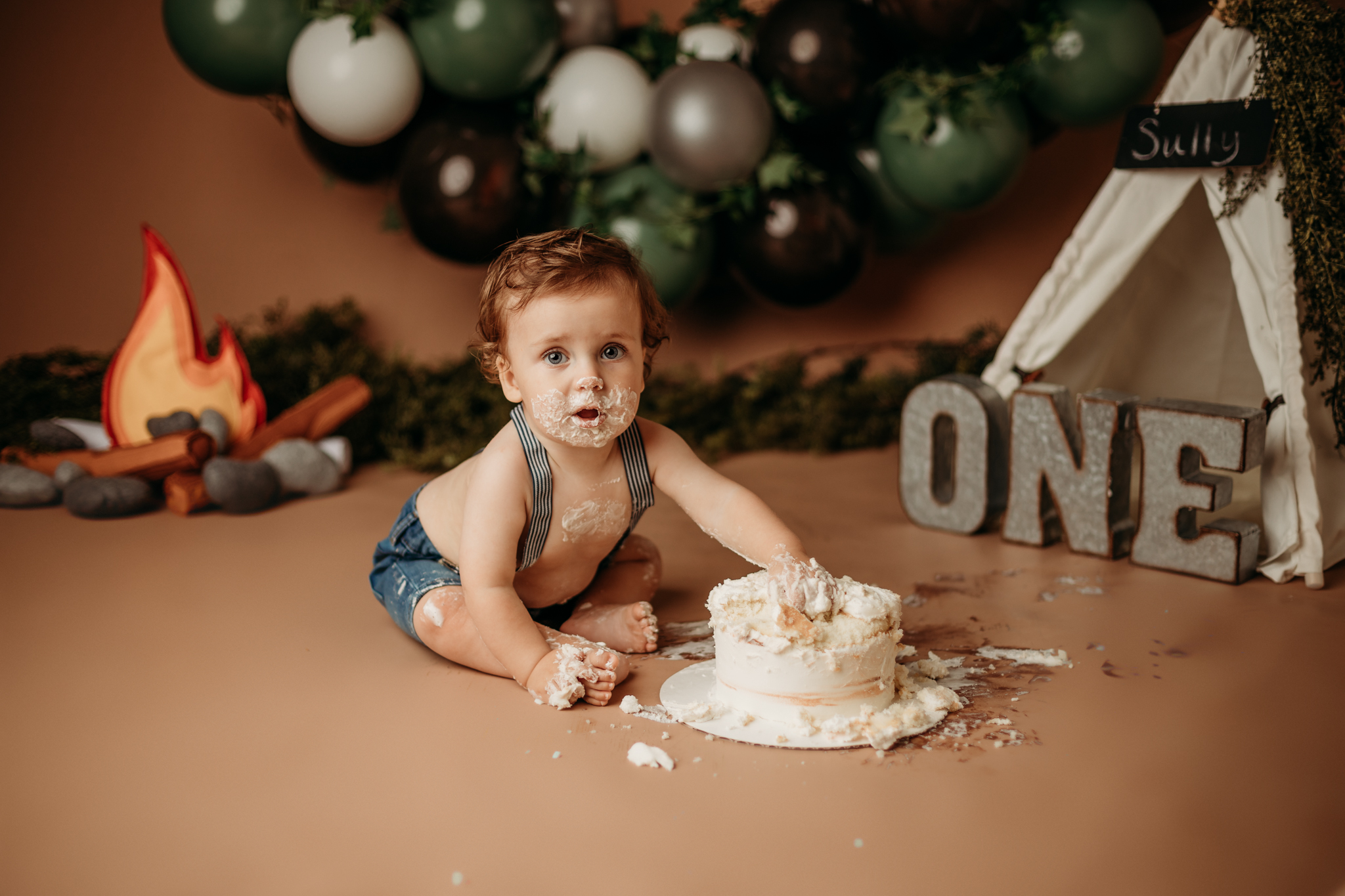 NWA one year images in studio with toddler on brown backdrop with a tent behind him and him eating cake while looking at the camera