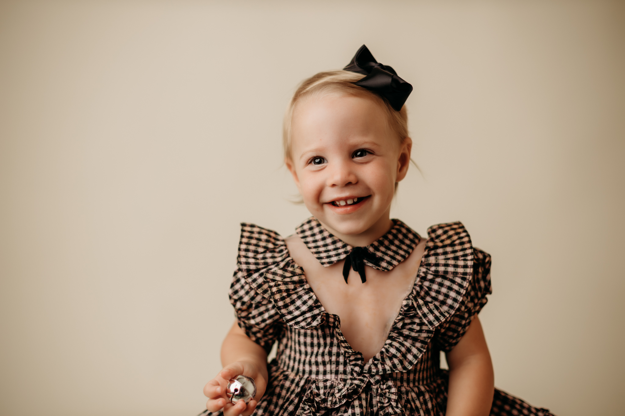 nwa childrens photography in studio with child smiling at camera against a cream backdrop and wearing a family heirloom dress