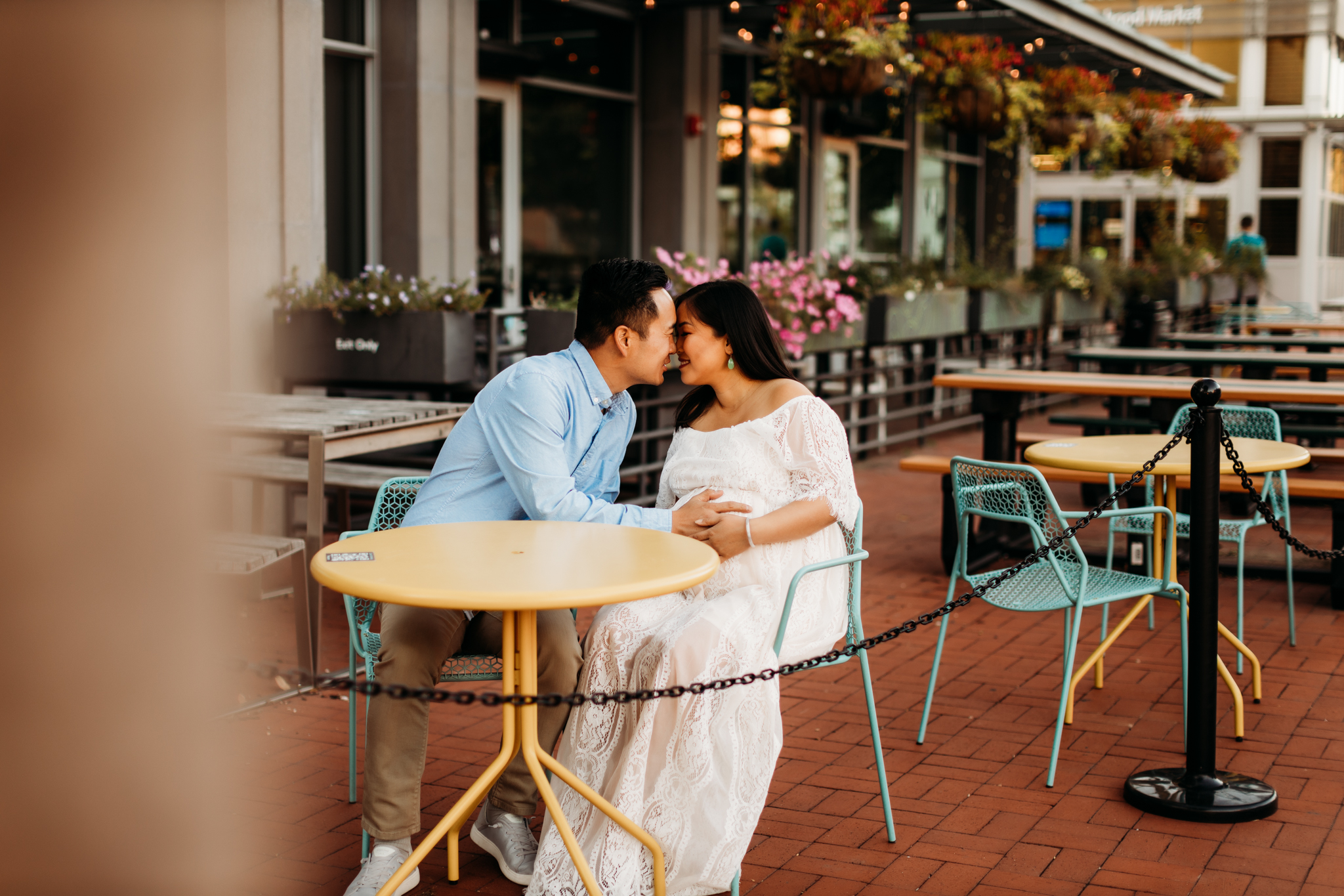 husband and wife sitting at a yellow streetside table going in for a kiss while holding their baby belly.